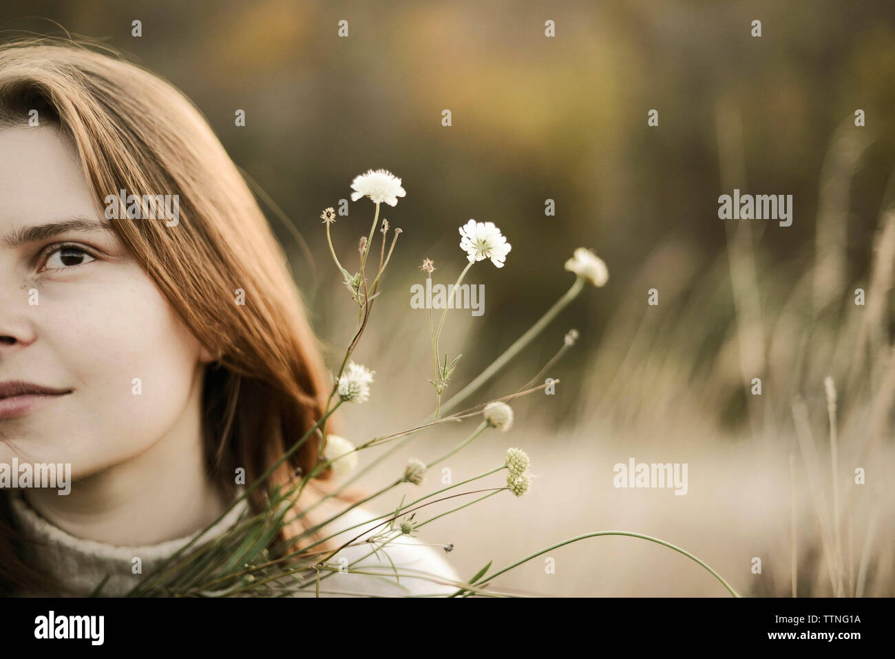 Jeune fille à l'extérieur de bouquet de wildlowers. Banque D'Images
