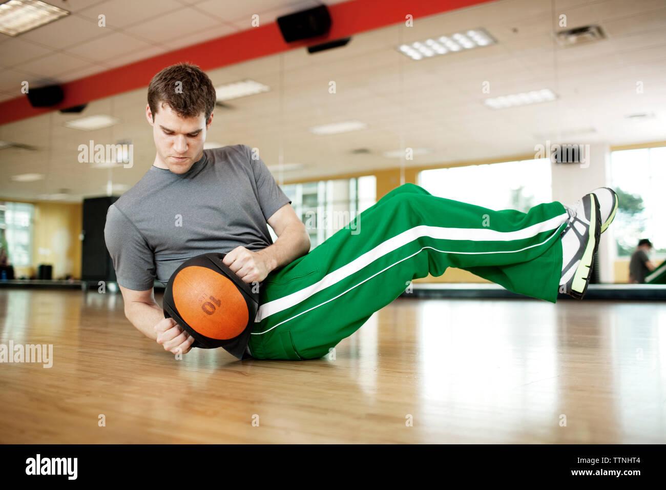 Jeune homme tenant le poids tout en exerçant en salle de sport Photo Stock