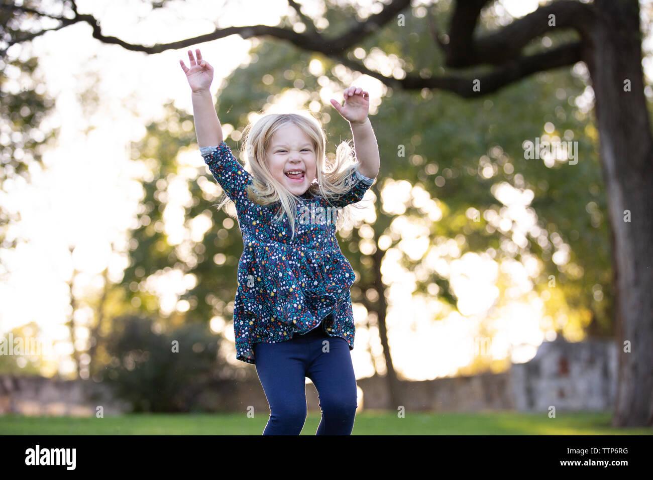 Fille blonde sauter avec les bras dans l'air extérieur et grand sourire Banque D'Images