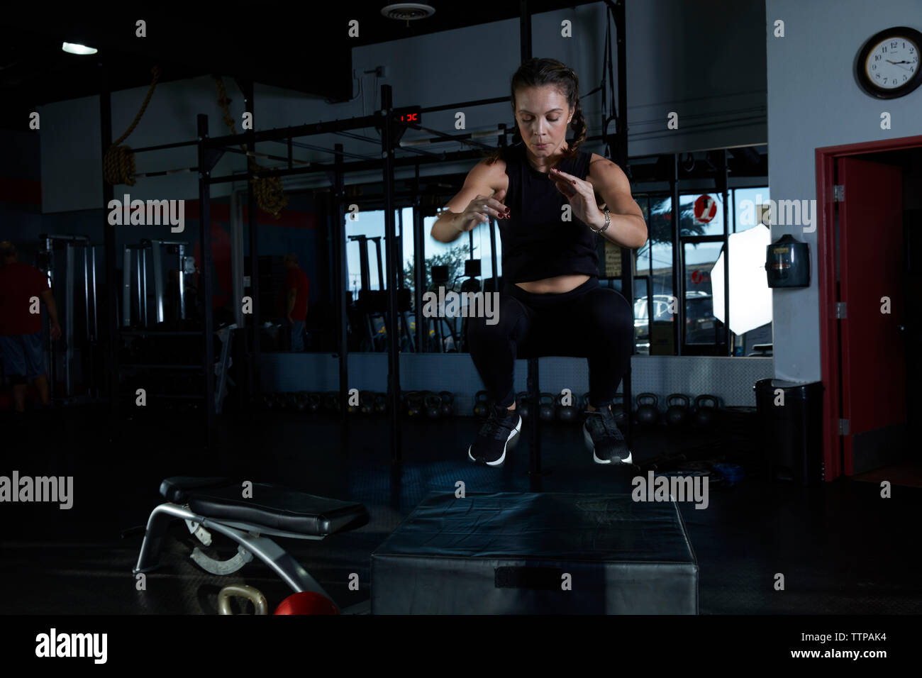 Femme sautant sur l'équipement d'exercice à la salle de sport Photo Stock