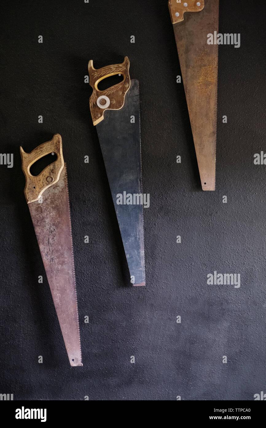 Old rusty scies à main accroché au mur Banque D'Images