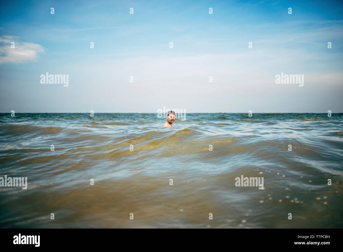 Boy swimming in sea against sky Banque D'Images