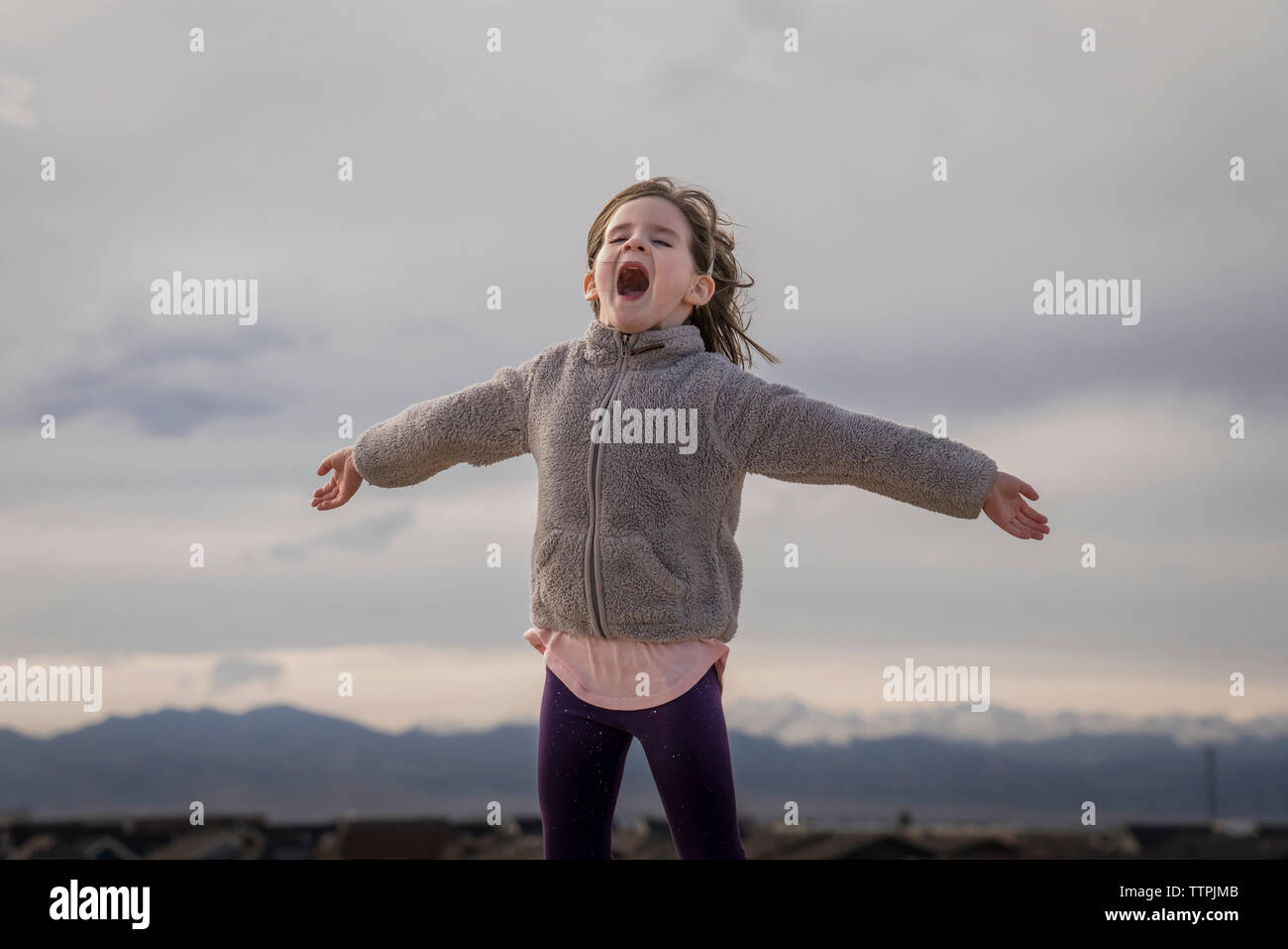 Happy girl with arms outstretched hurlant debout contre ciel nuageux Banque D'Images