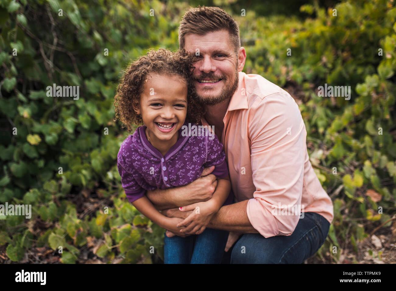 Portrait du Père embrassant heureux fille tout en s'agenouillant contre des plantes dans le parc Banque D'Images