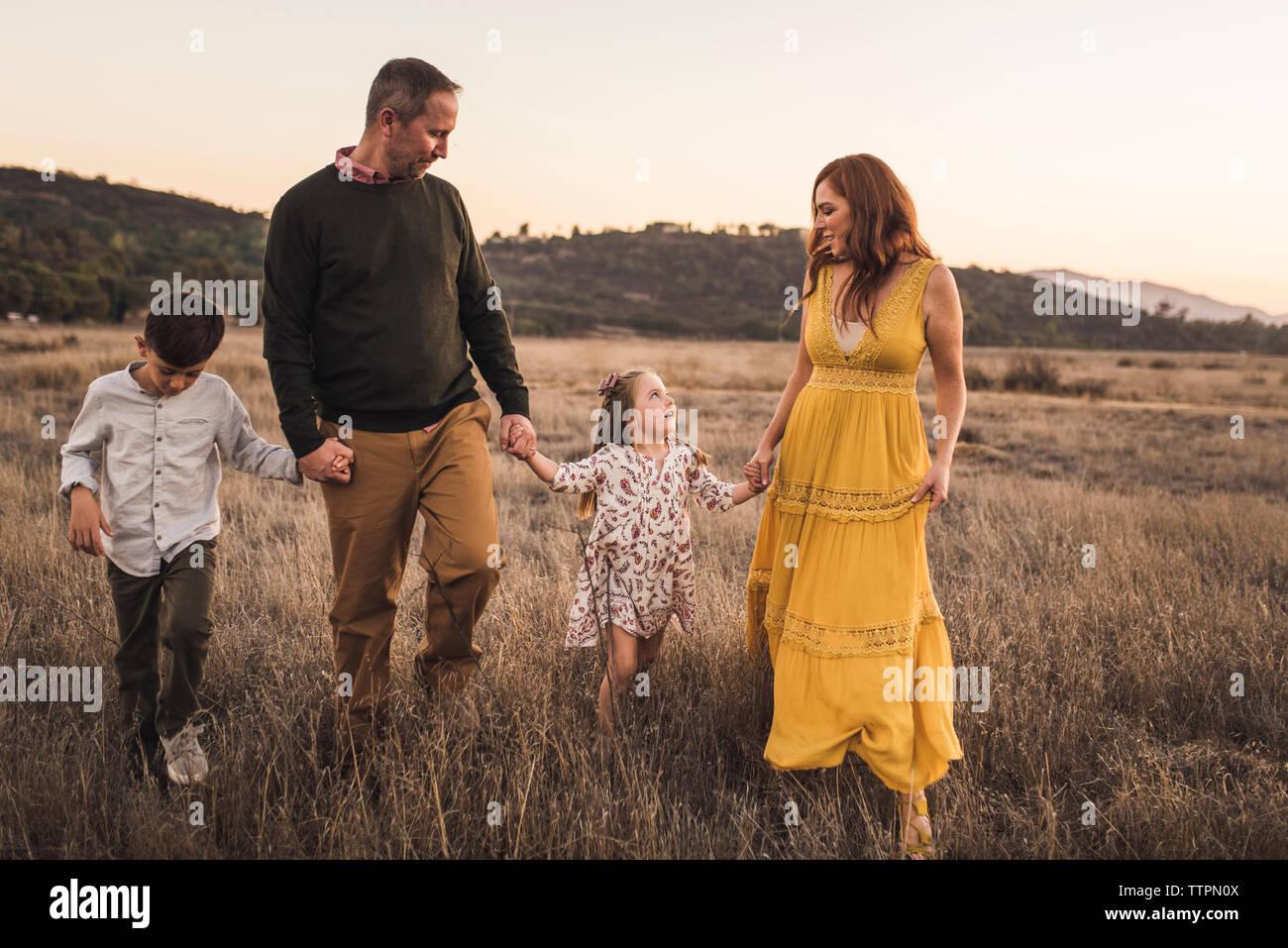 Jeune famille tenant la main tout en marchant en Californie field at sunset Banque D'Images