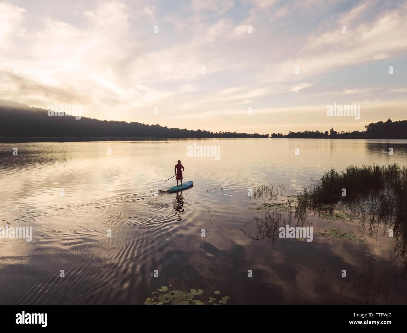 Une femelle paddleboarding sur un lac Banque D'Images