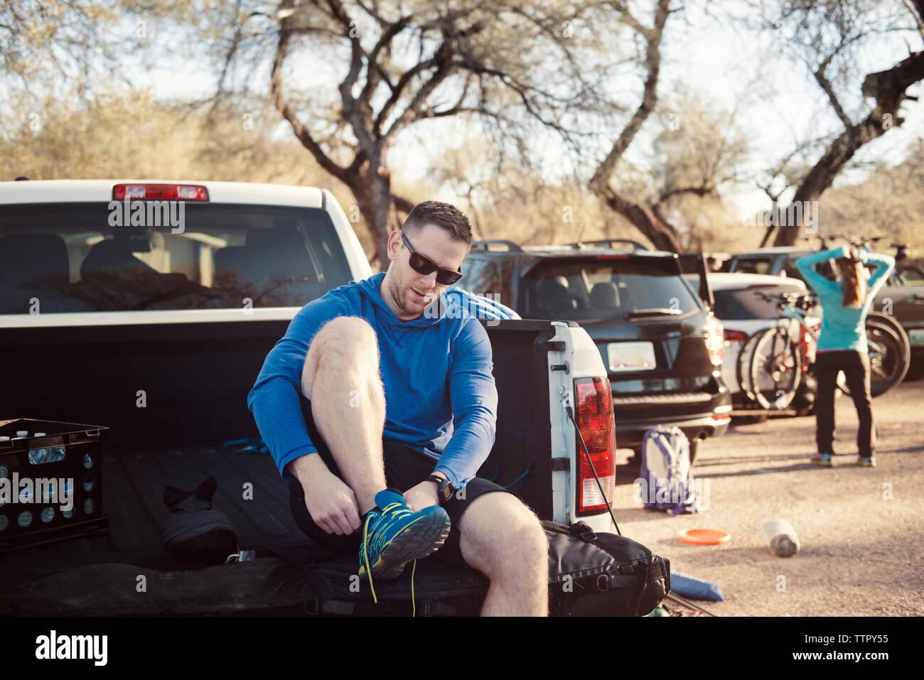 Homme portant la chaussure de sport tout en restant assis dans la camionnette Photo Stock