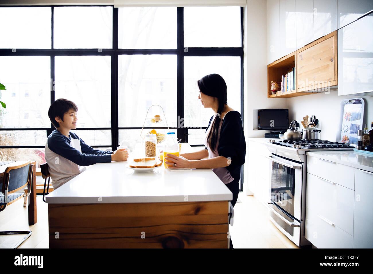 La mère et le fils manger le petit déjeuner sur la table de cuisine bien éclairées. Banque D'Images