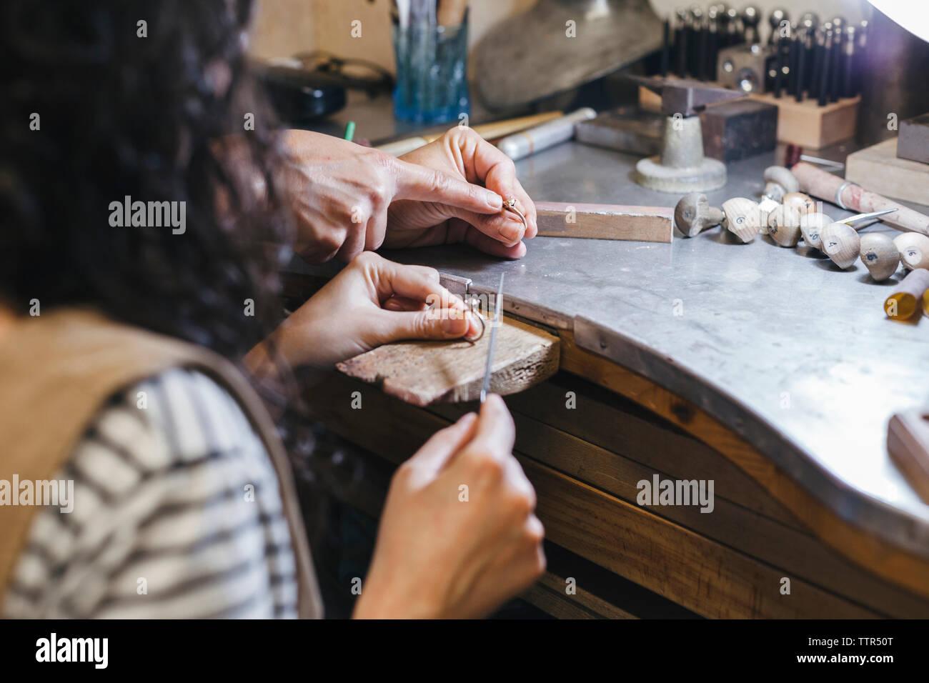 Les mains coupées de l'enseignement enseignant étudiant à l'anneau de forme sur la table à l'atelier Banque D'Images