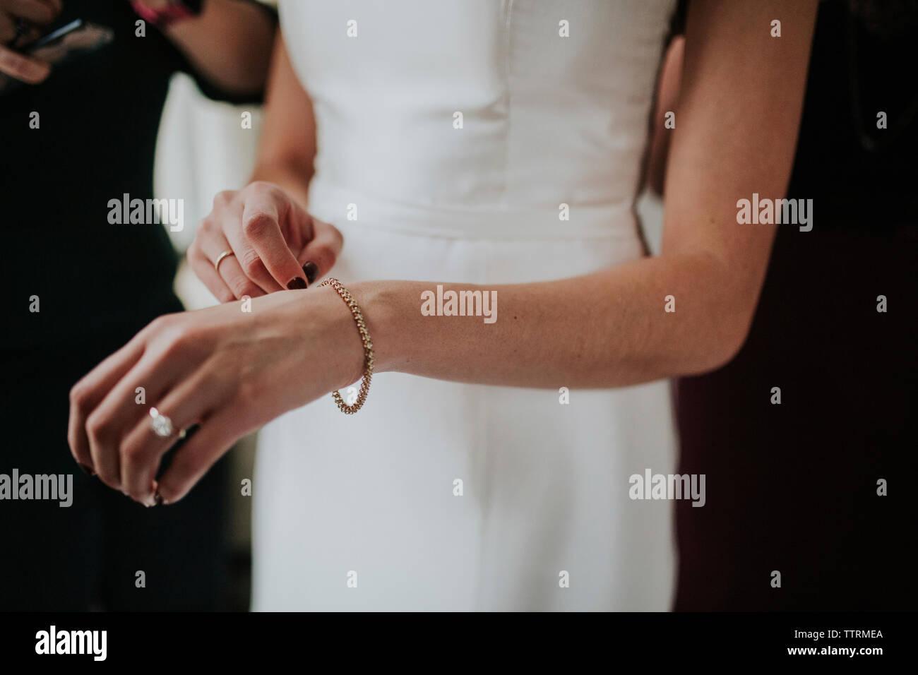 Au milieu du port de mariée robe de mariage et bracelet Photo Stock