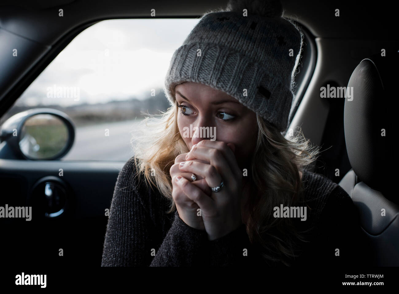 Close-up of woman with hands clasped looking away while sitting in car Banque D'Images