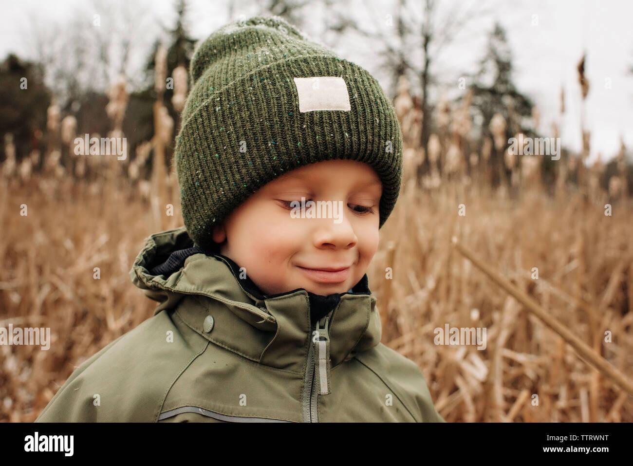 Portrait of young boy smiling en hiver avec chapeau et manteau dans la neige Banque D'Images
