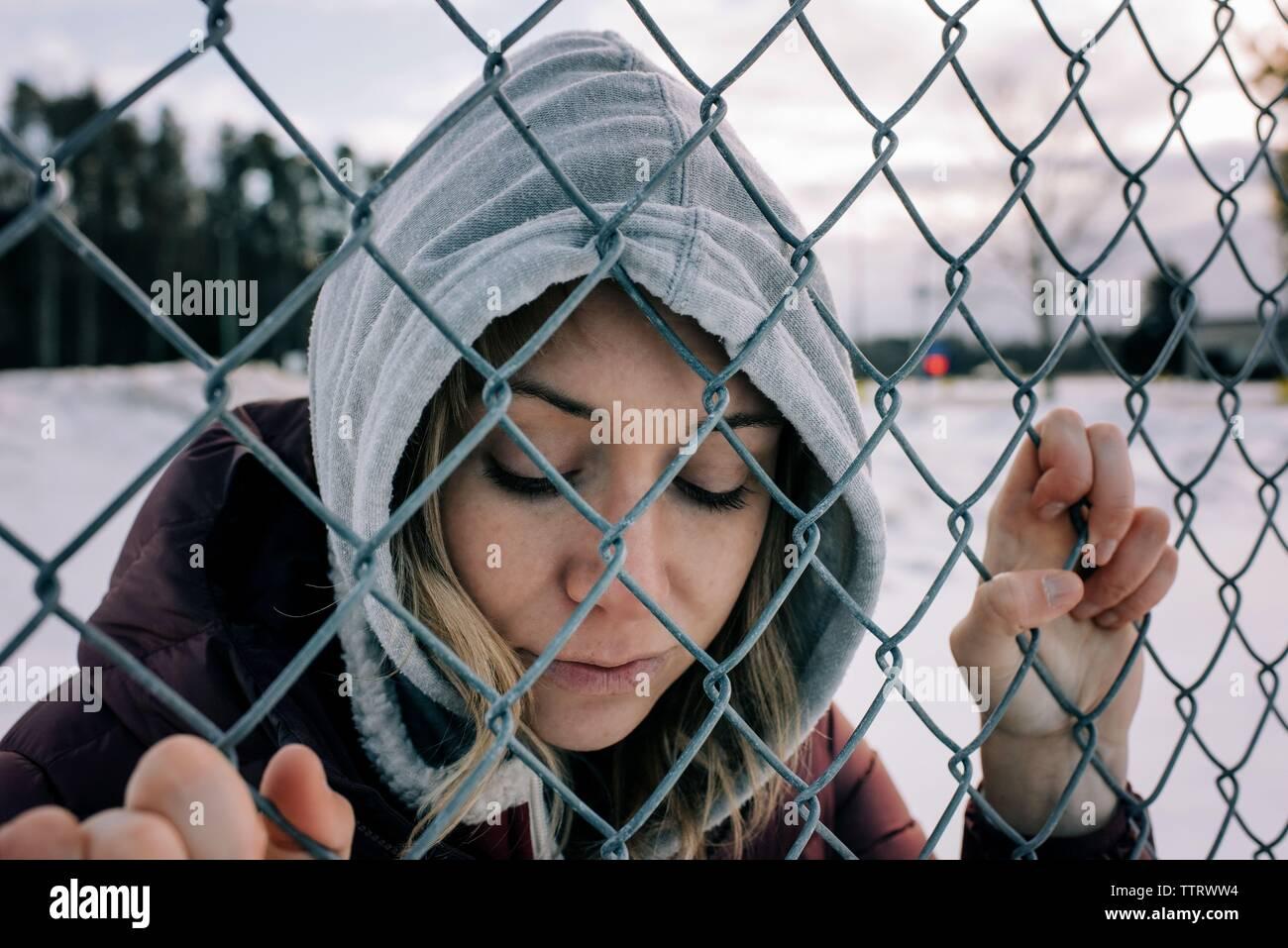 Portrait de femme tenant une clôture métallique avec son capot en hiver Banque D'Images