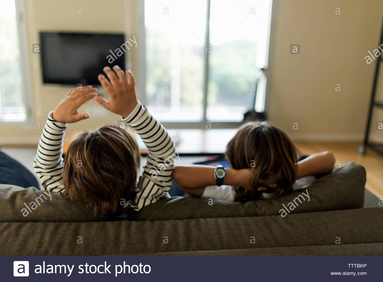 Deux enfants de dos assis sur le canapé à jouer avec une tablette Banque D'Images