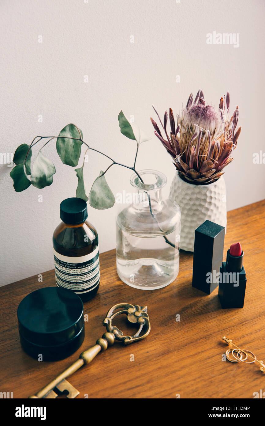 Portrait de produits de beauté avec vase de fleurs sur table Banque D'Images