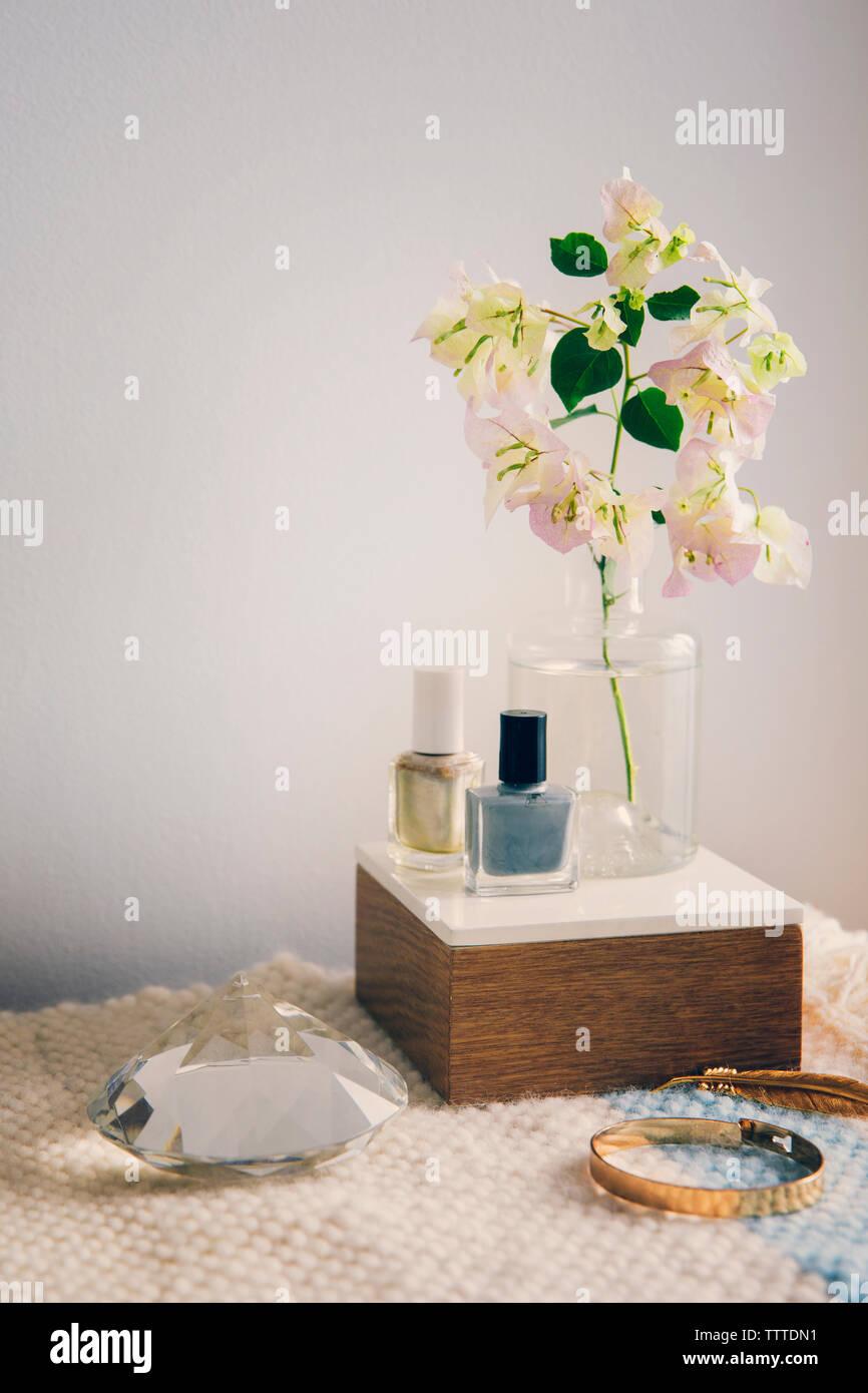 Vernis à ongles avec des bijoux en cristal et par vase à fleurs sur table Banque D'Images