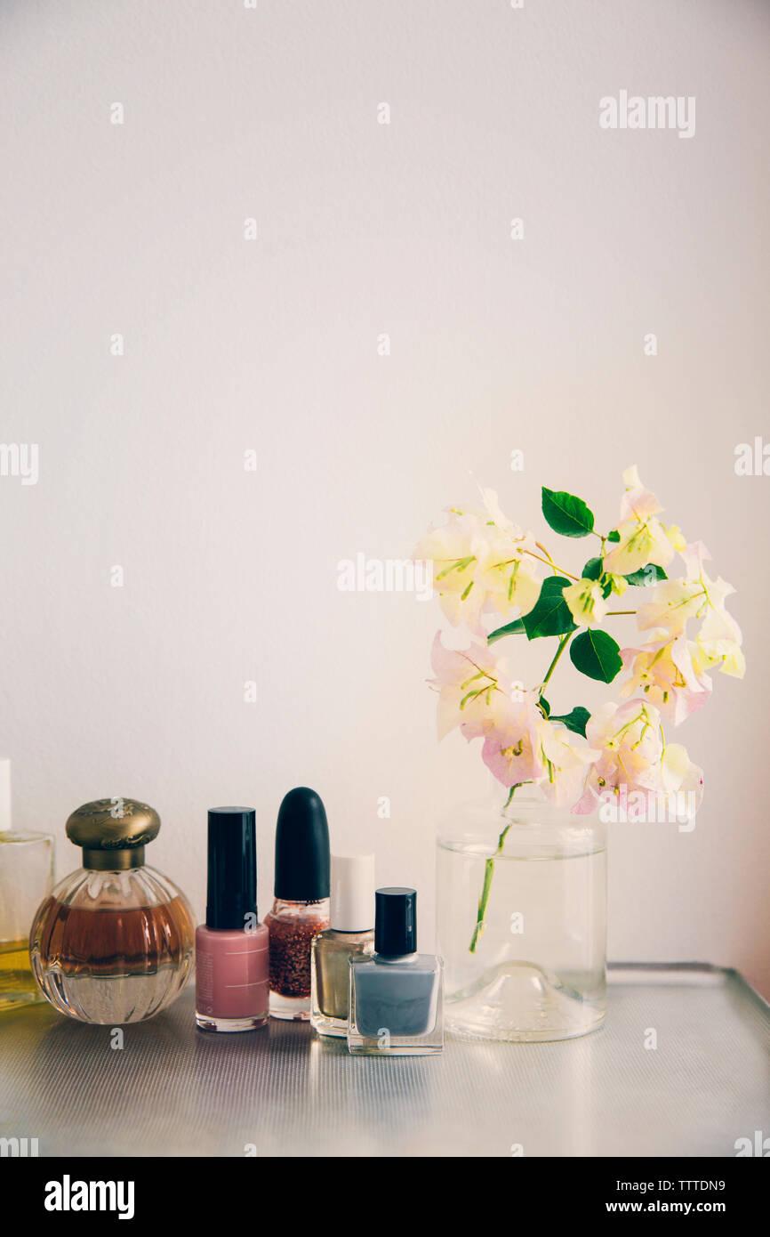 Produits de beauté organisé par vase à fleurs sur table Banque D'Images