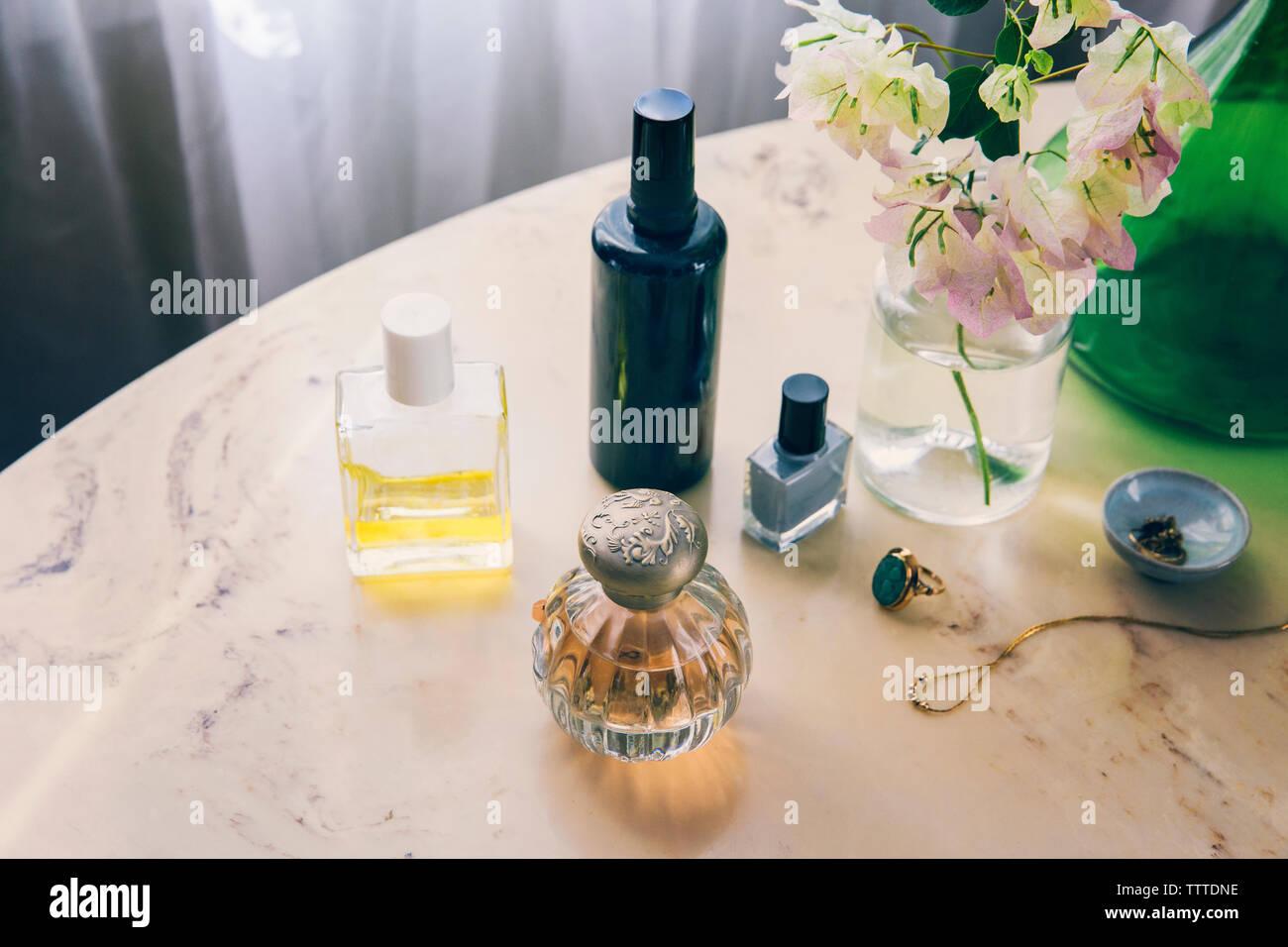 Portrait de produits de beauté avec des bijoux par vase à fleurs sur table Banque D'Images