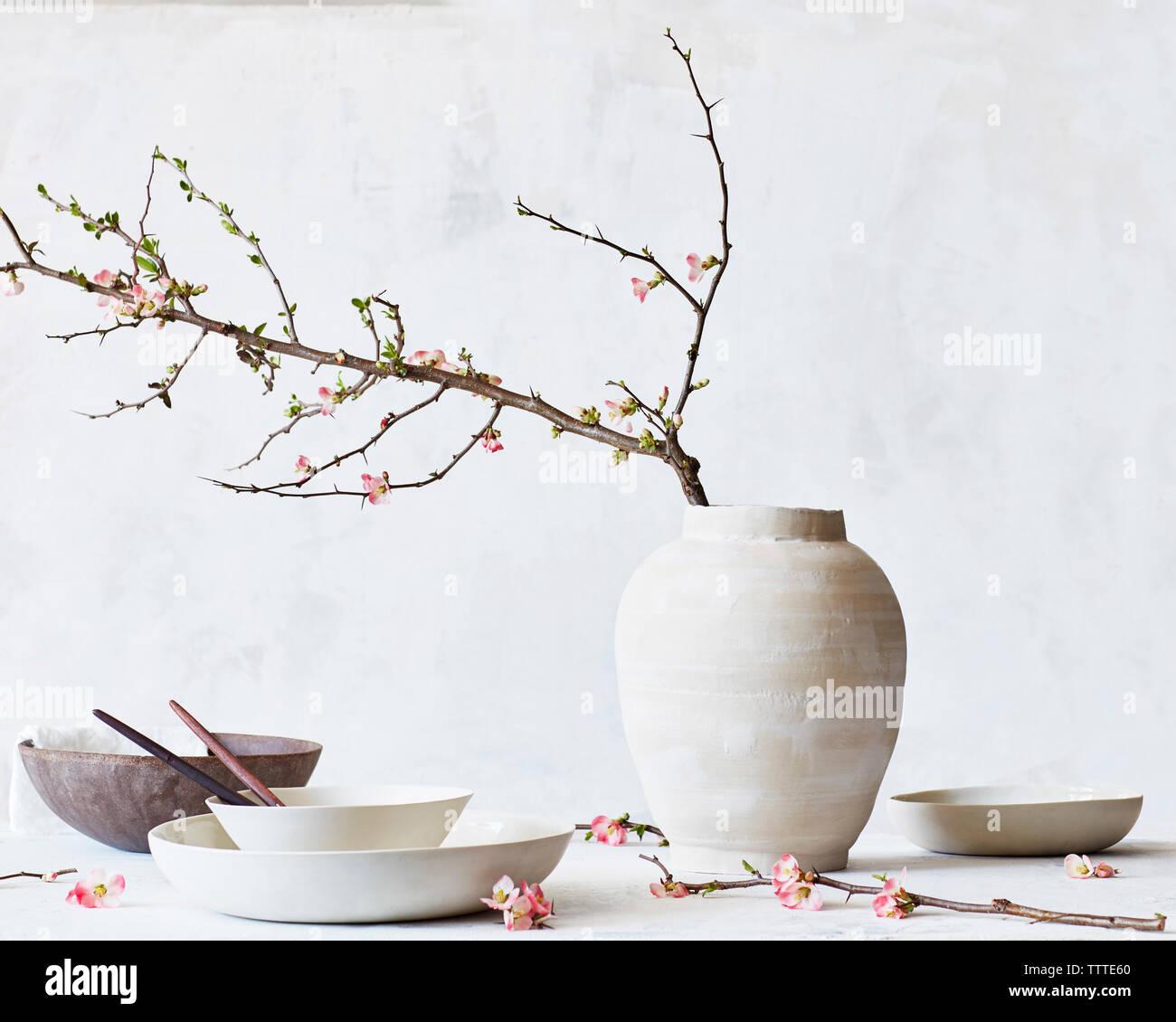 Vase à fleurs avec des bols et des assiettes sur la table contre le mur Banque D'Images