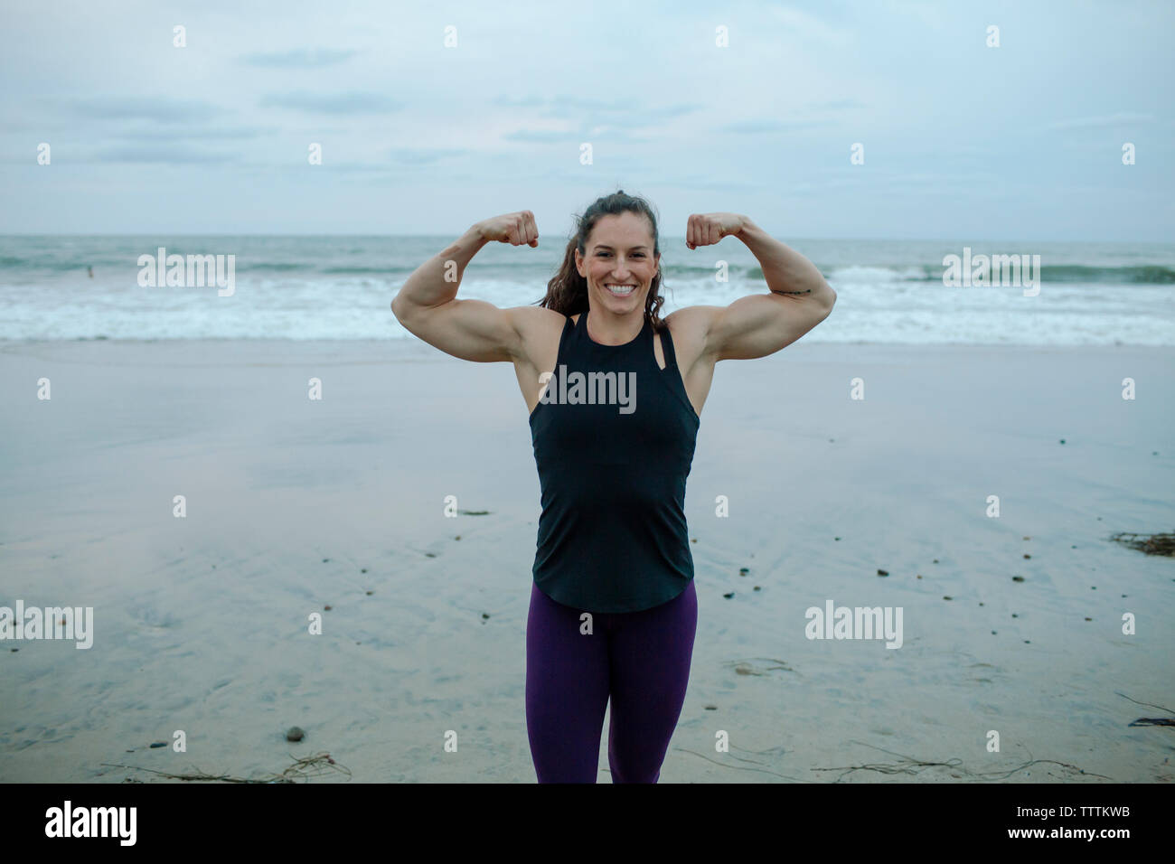 Portrait of woman flexing muscles construction musculaire at beach Photo Stock