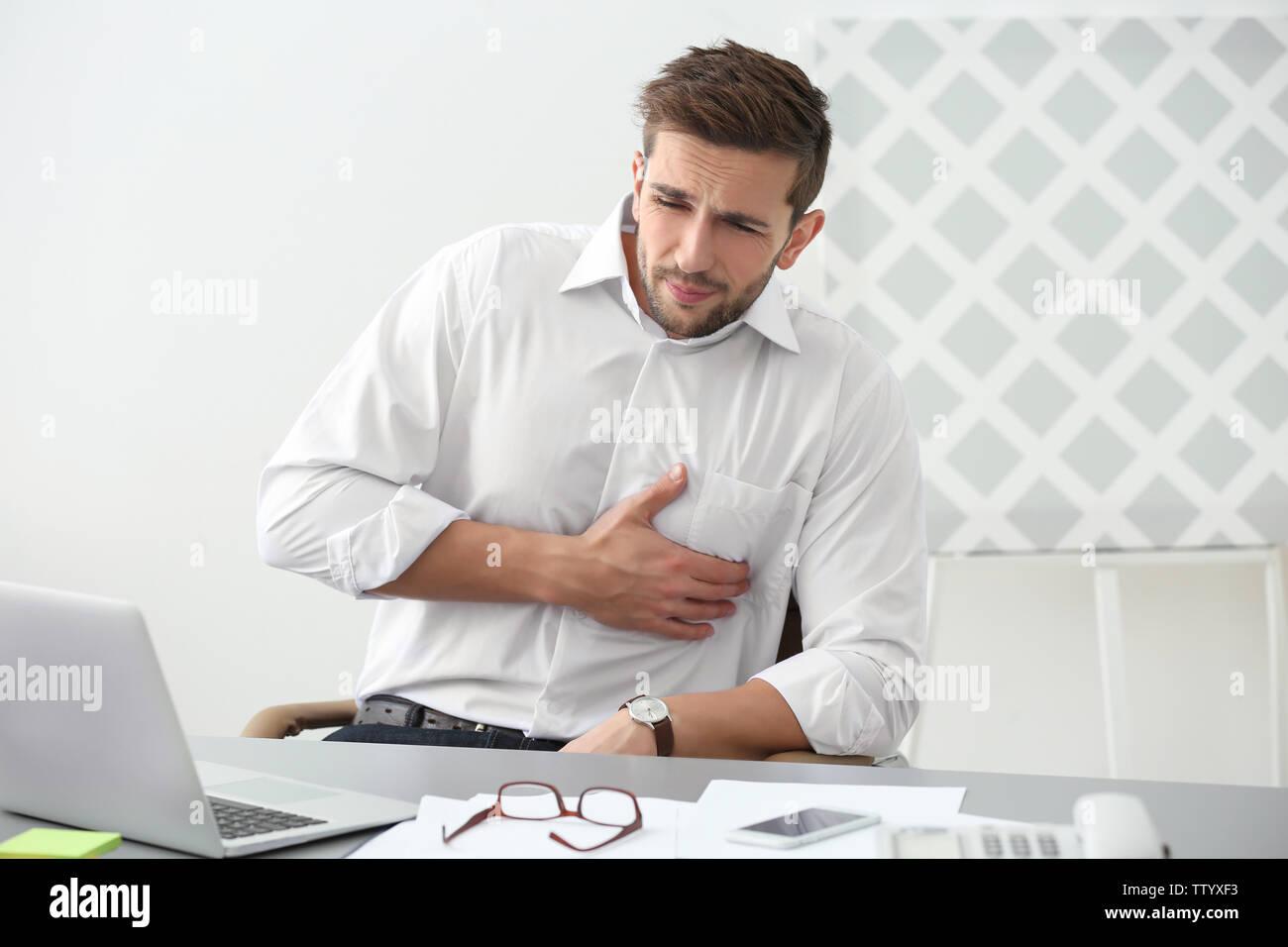 Beau jeune homme souffrant de chagrin dans office Photo Stock