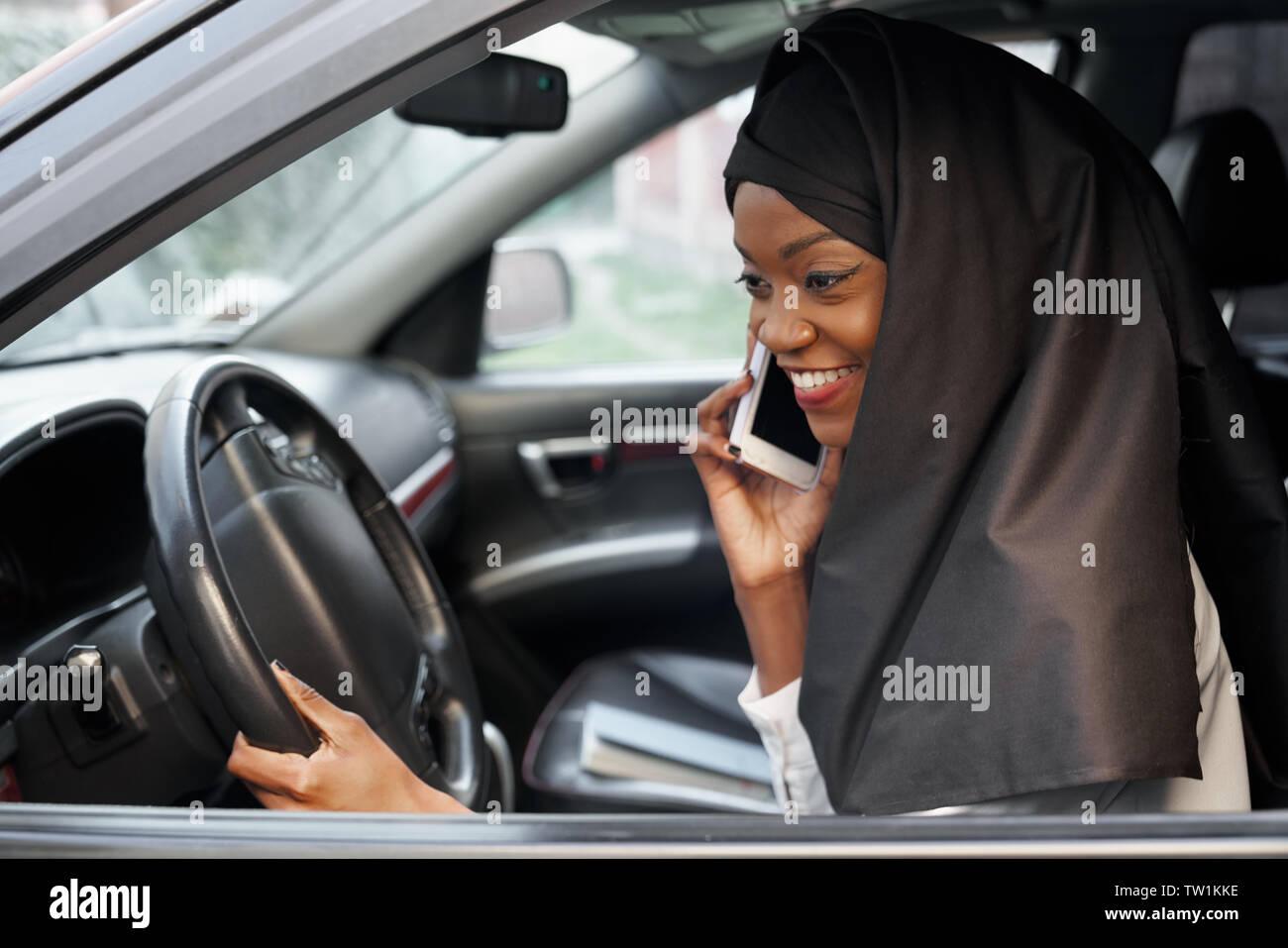 L'Afrique de l'élégante femme musulmane portant le hijab en noir assis dans l'automobile, de parler par téléphone mobile. Belle, jeune fille tenant la main sur le volant, en souriant. Banque D'Images