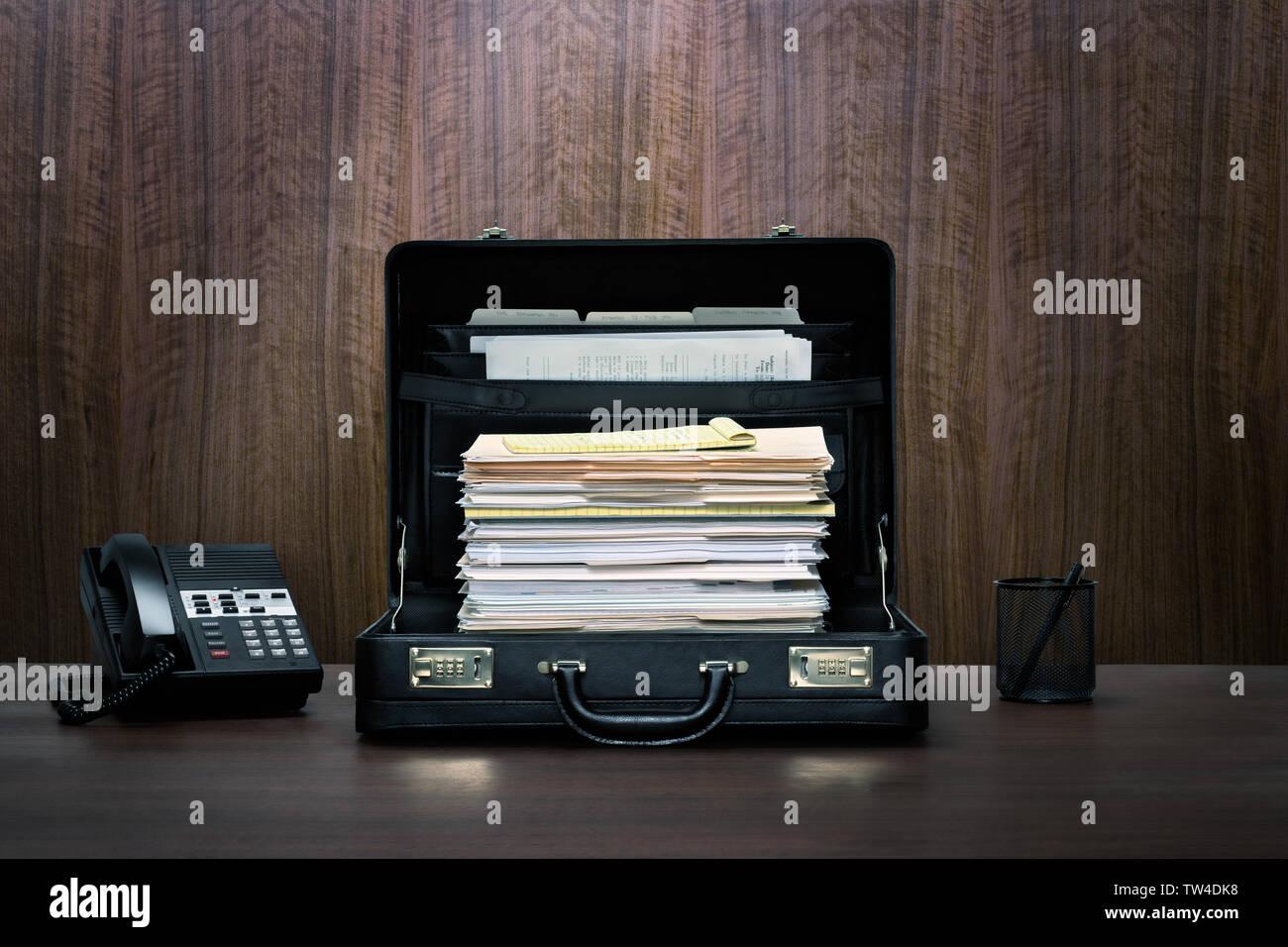 Et la surcharge de travail ambitieux, grande cheminée de fichiers et dossiers dans une valise en cuir noir sur bois bureau avec téléphone et panneau arrière-plan Photo Stock