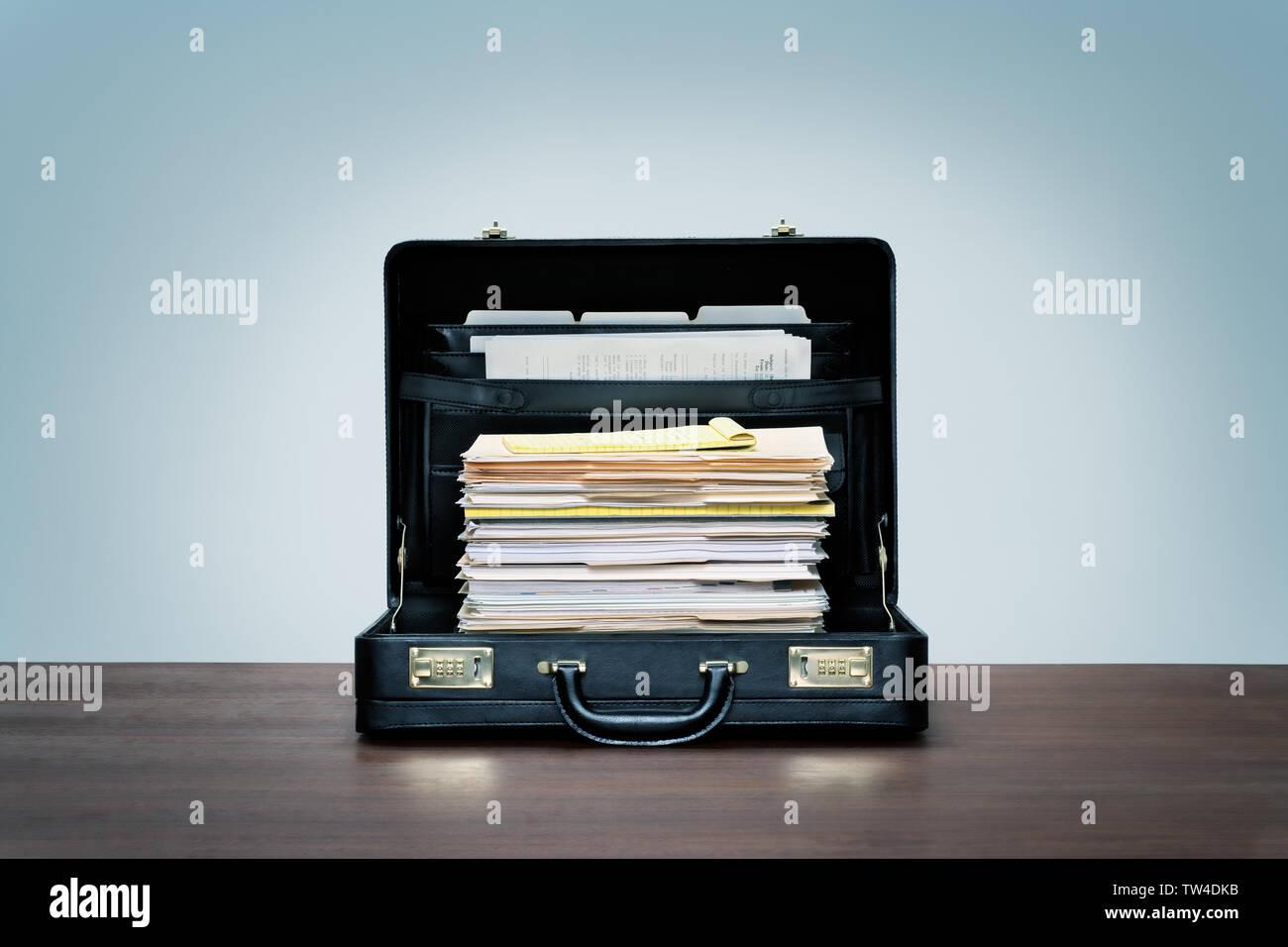 Grande cheminée de fichiers et dossiers dans une valise en cuir noir sur bois 24 avec fond bleu. Photo Stock