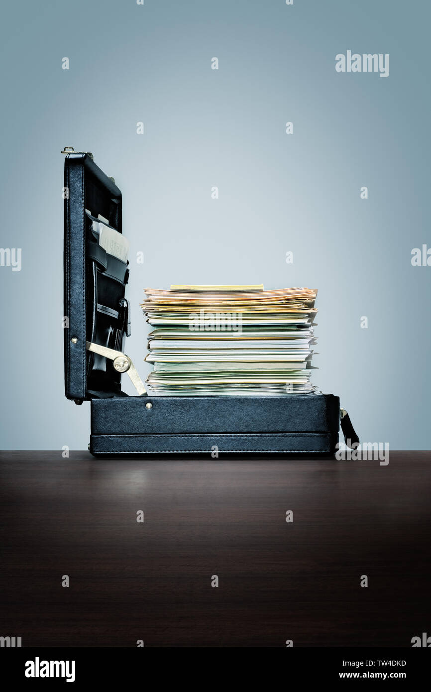 Compusive surmenage, bourreau de travail. Pile de fichiers et dossiers en porte-documents. sur le bureau en bois sombre avec fond bleu Photo Stock