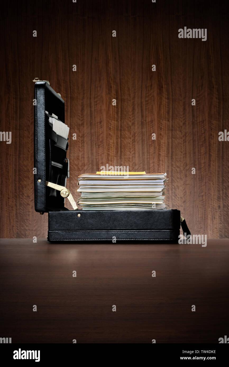 Housse Attache en cuir noir avec grande cheminée de fichiers et dossiers de bureau en bois sombre avec des lambris background Photo Stock