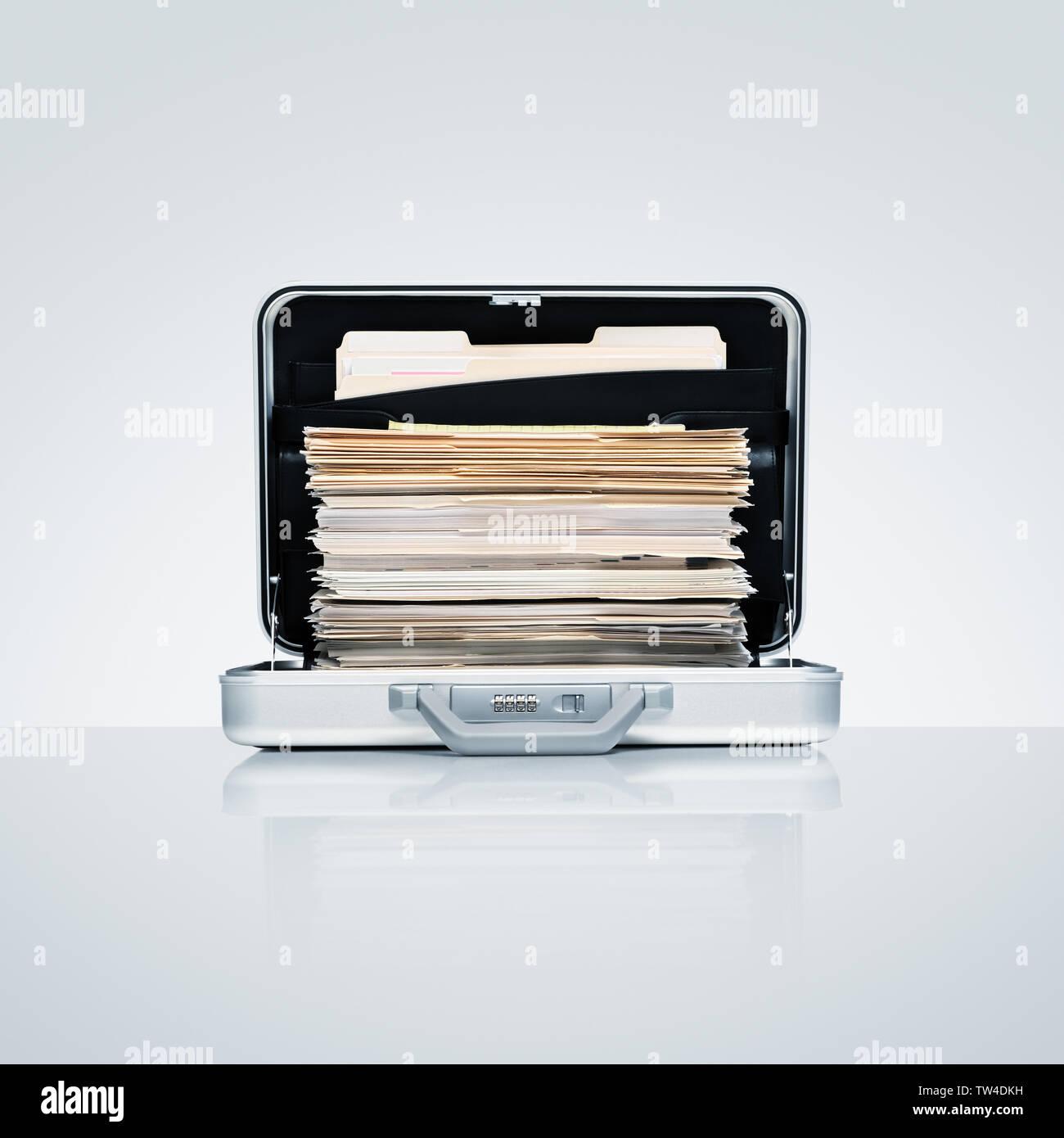 Mallette en aluminium avec pile ambitieux des fichiers et dossiers sur la surface en aluminium gris froid avec réflexion subtile Photo Stock