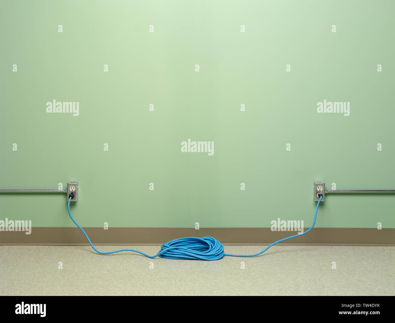 Câblage électrique dangereuse spirale bleu avec rallonge branchée sur deux AC prises murales sur mur vert Banque D'Images