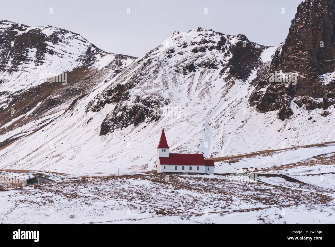 Petite église située au sommet d'une colline, offrant une vue pittoresque sur l'océan et le village de Vik. Banque D'Images