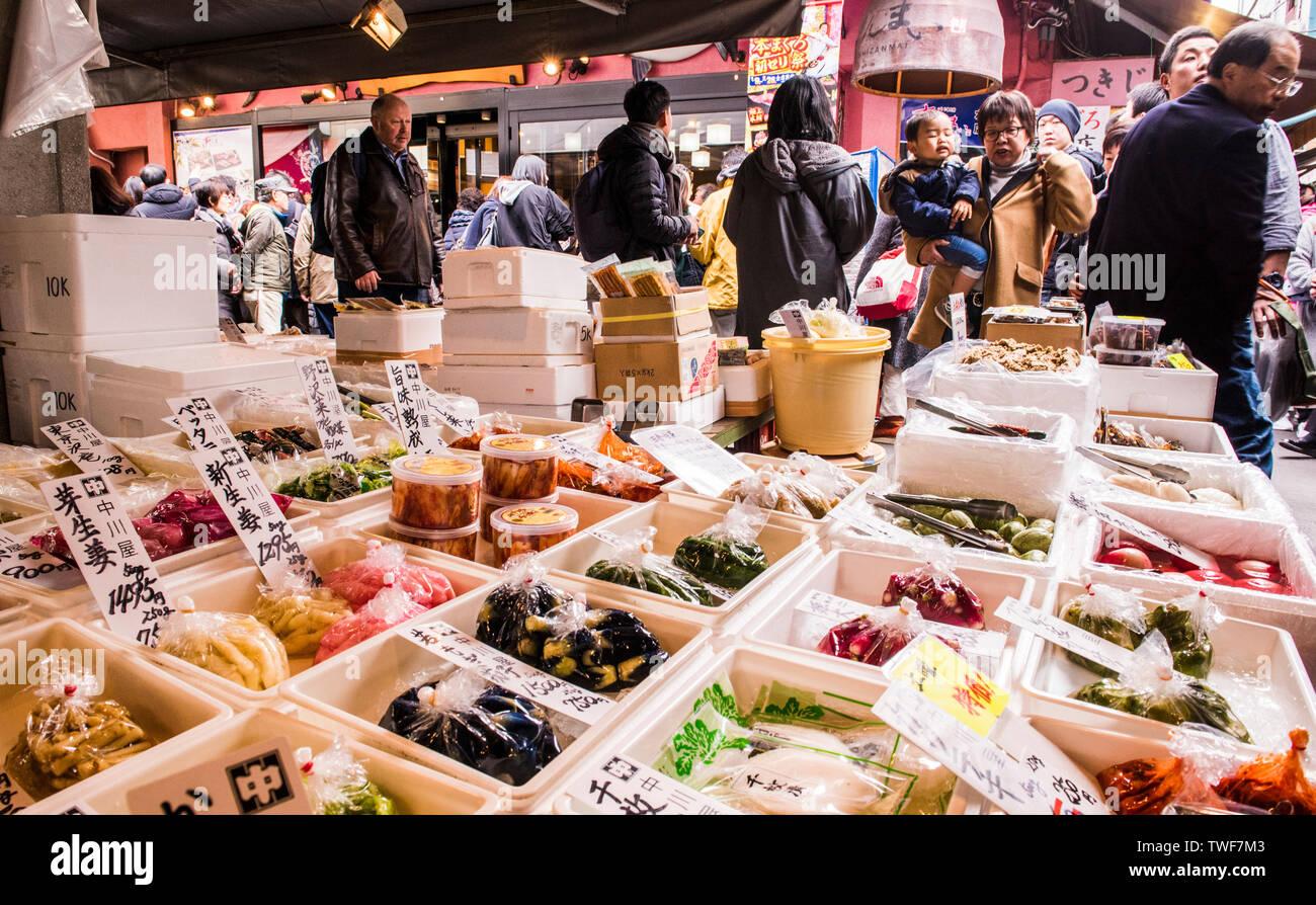 Affichage de la nourriture fraîche et des gens qui marchent à travers dans le marché aux poissons de Tsukiji à Tokyo au Japon. Banque D'Images