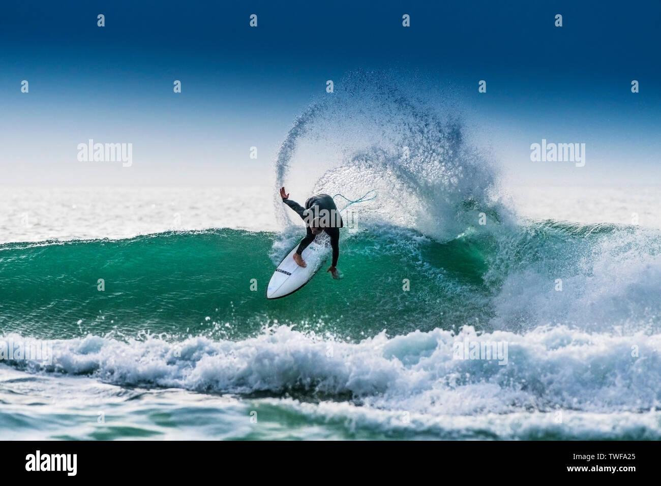 Un surfeur équitation un surf sur la crête d'une vague de couleur jade dans Fistral Newquay à à Cornwall. Banque D'Images