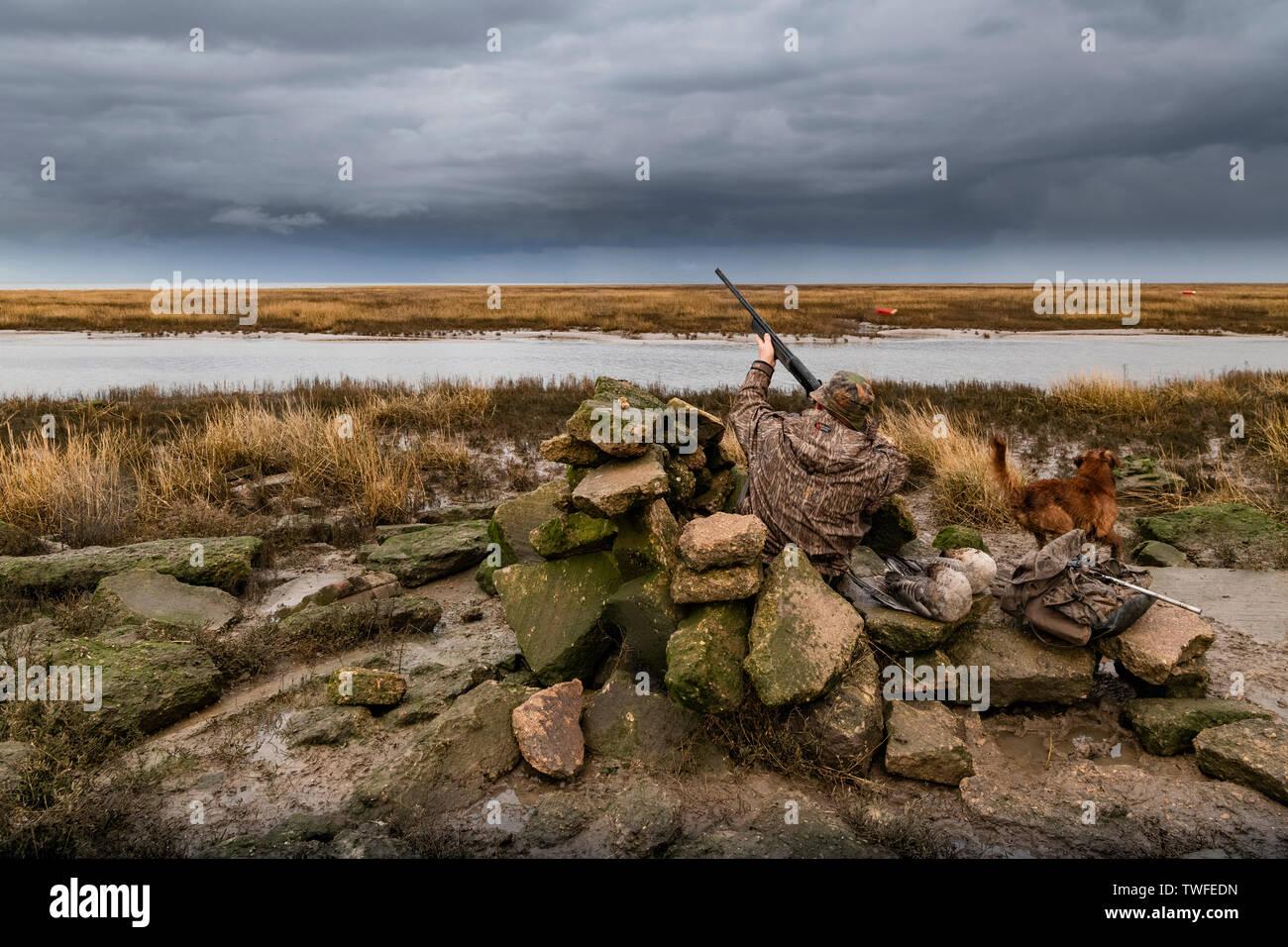 Un homme sur le tournage de lavage Lincolnshire sur les marais d'oies à partir d'un tournage masquer avec les nuages de tempête et de la pluie. Photo Stock