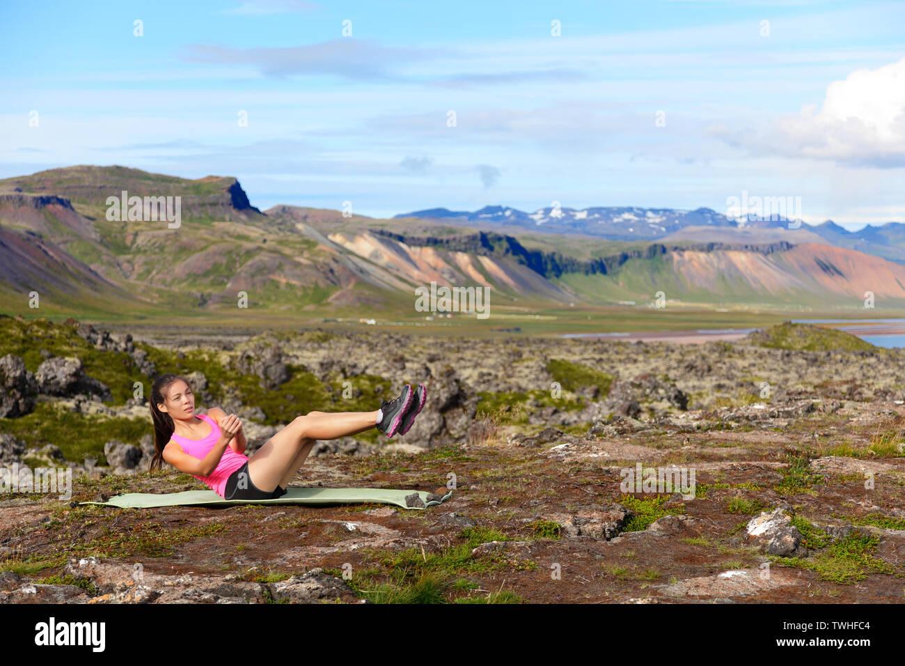 Femme Fitness core twist russe faisant de l'exercice à l'extérieur. Mettre en place la formation des femmes dans l'estomac nature paysage incroyable sur l'Islande. Mettre en place le sport féminin fille modèle crossfit à l'extérieur. De Formation Athlète de race mixte. Photo Stock