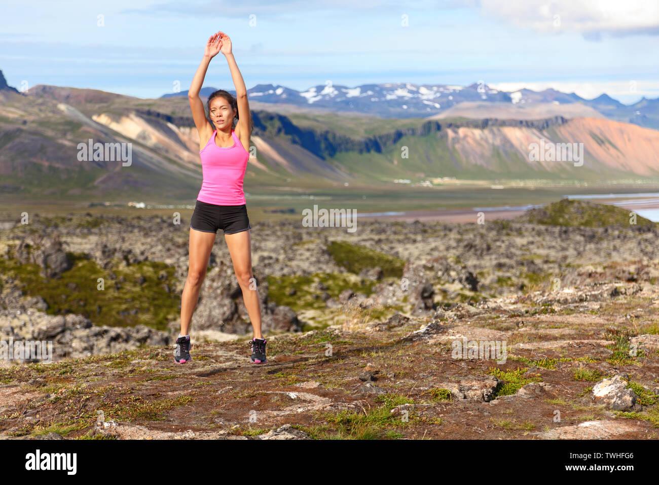 Femme Fitness jumping vous exercez à l'extérieur faisant sauter accroupi dans amazing nature paysage. Mettre en place l'athlète féminine de la formation croisée à l'extérieur. Libre à partir de l'Islande. Photo Stock