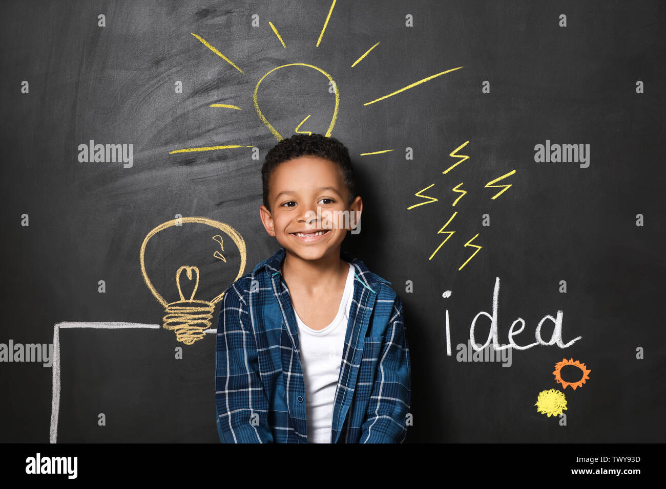 Garçon afro-américaine près de dessiné sur le mur sombre ampoules Photo Stock
