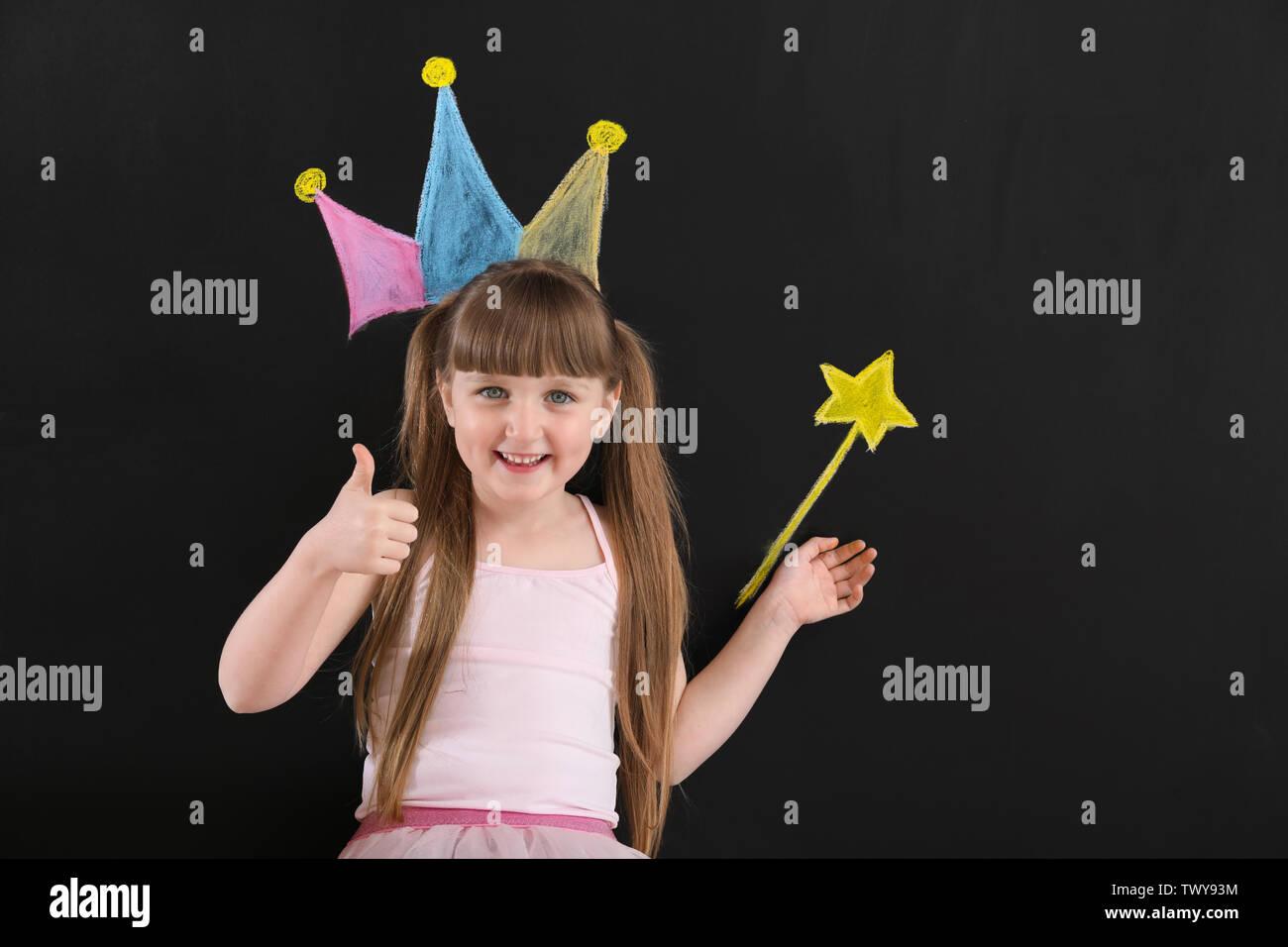 Cute little girl près de mur sombre dessiné avec couronne et baguette magique Photo Stock