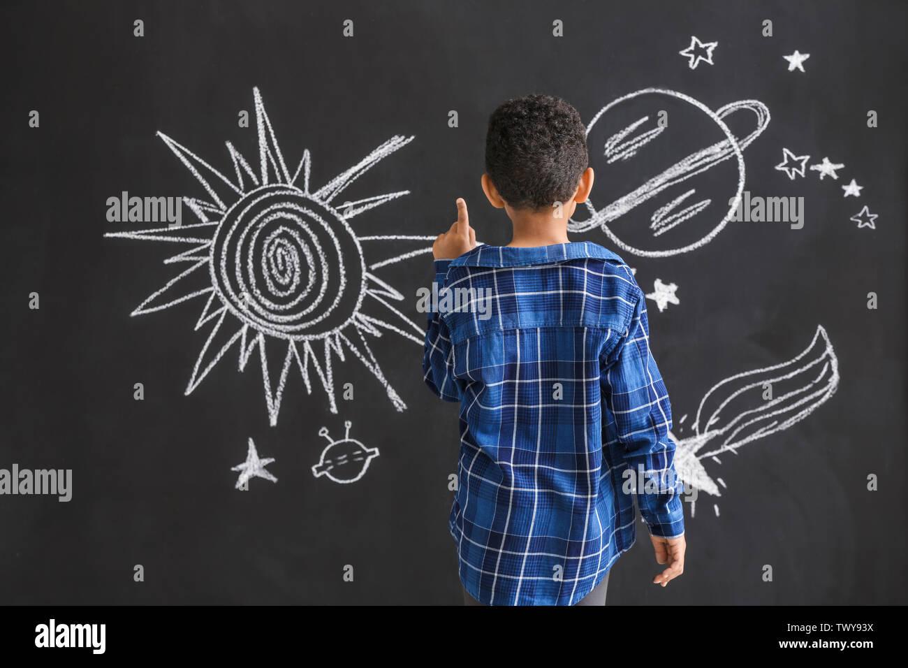 Garçon afro-américain de l'espace dessin mignon sur mur sombre Photo Stock