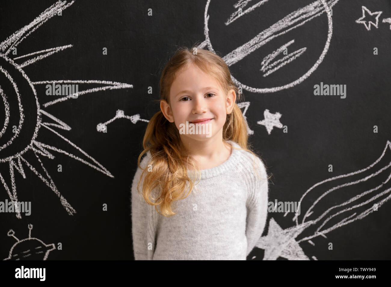 Petite fille près de l'espace dessiné avec mur sombre Photo Stock