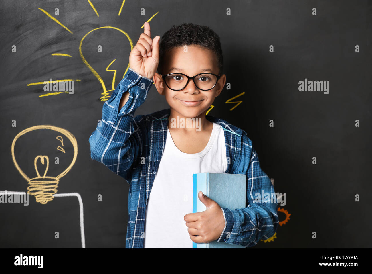 Garçon afro-américain avec l'index levé près de dessiné sur le mur sombre ampoules Photo Stock