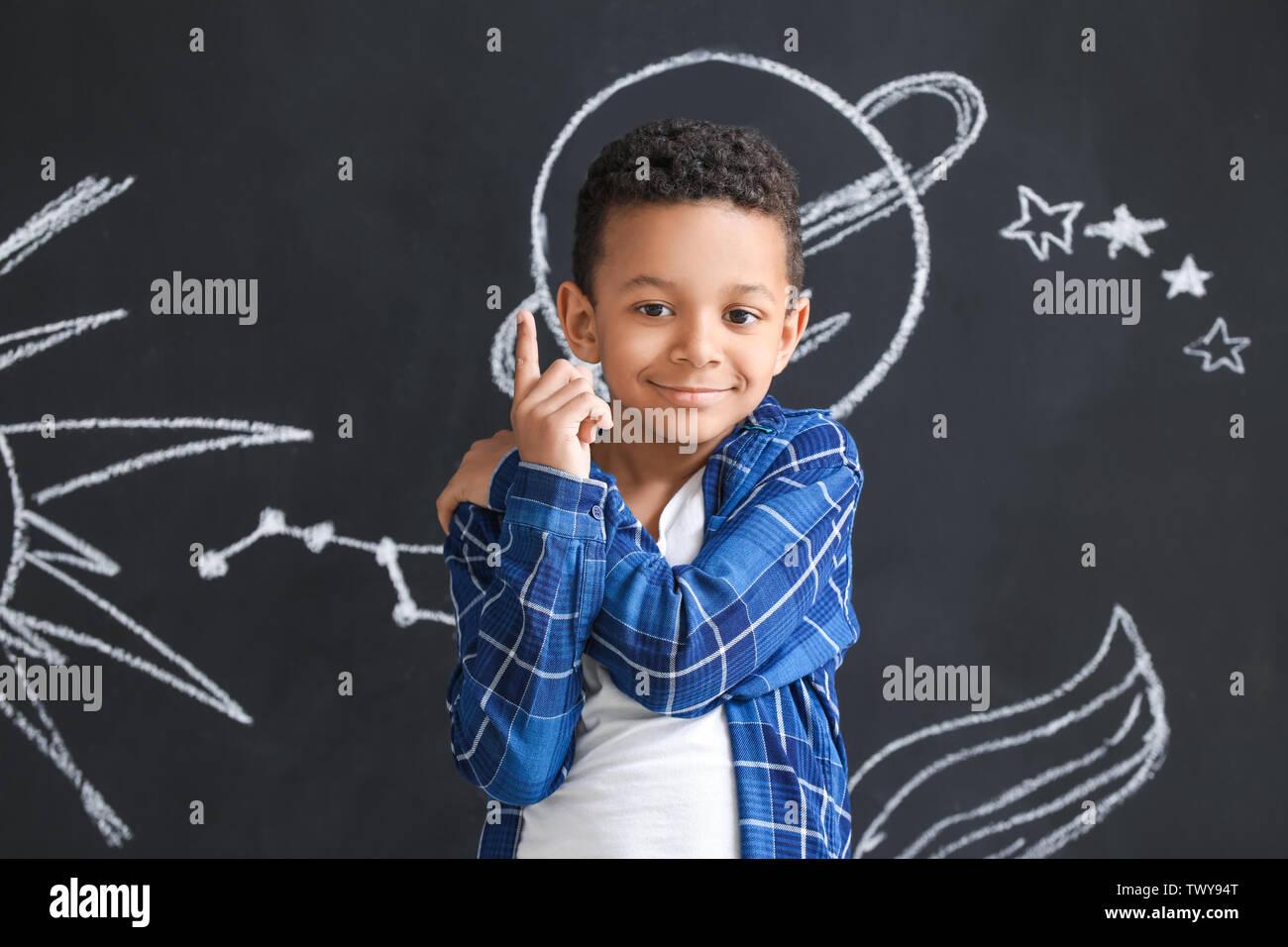 Mignon garçon afro-américaine près de mur sombre avec de l'espace dessiné Photo Stock