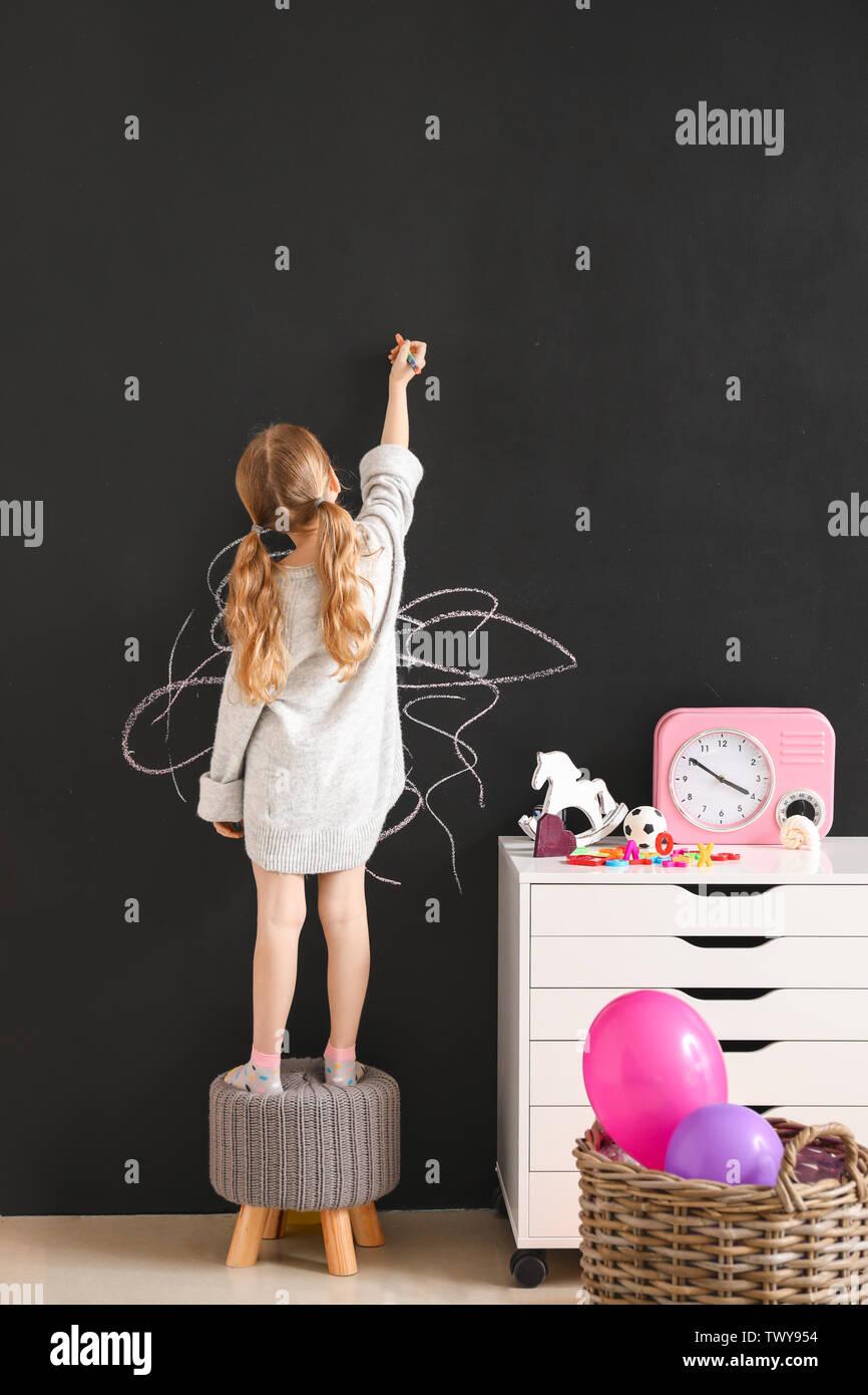 Petite fille dessin sur mur sombre dans la chambre Photo Stock