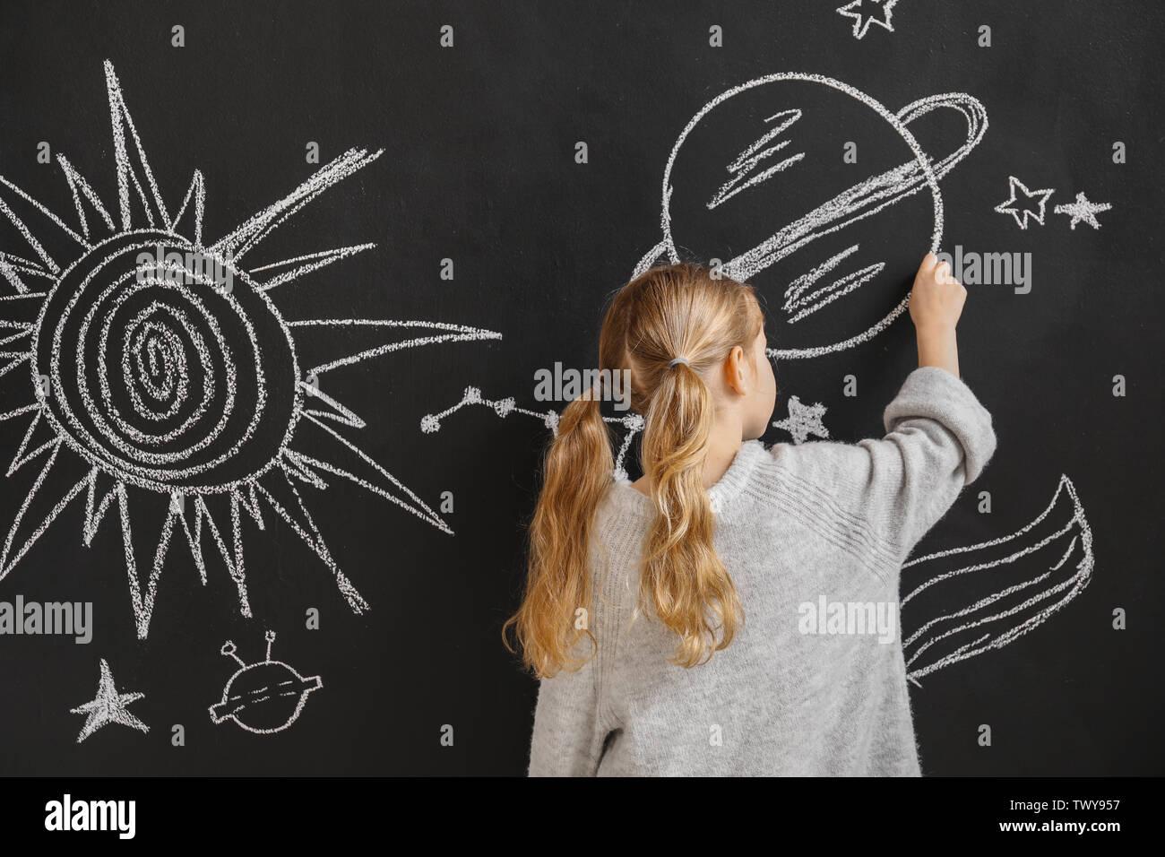Petite fille de l'espace dessin sur mur sombre Photo Stock
