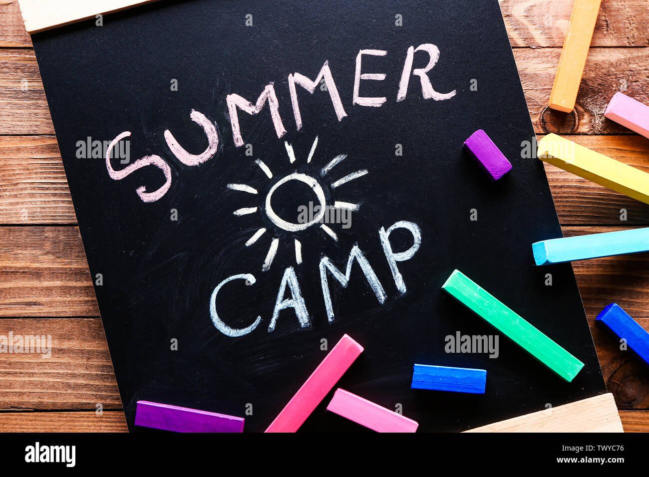 Tableau avec texte SUMMER CAMP et craies sur table en bois Photo Stock