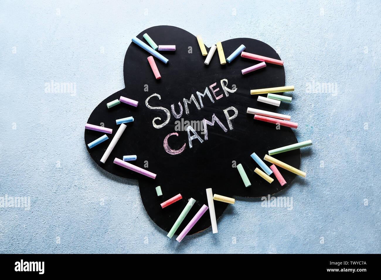 Tableau avec texte SUMMER CAMP et craies sur fond couleur Photo Stock