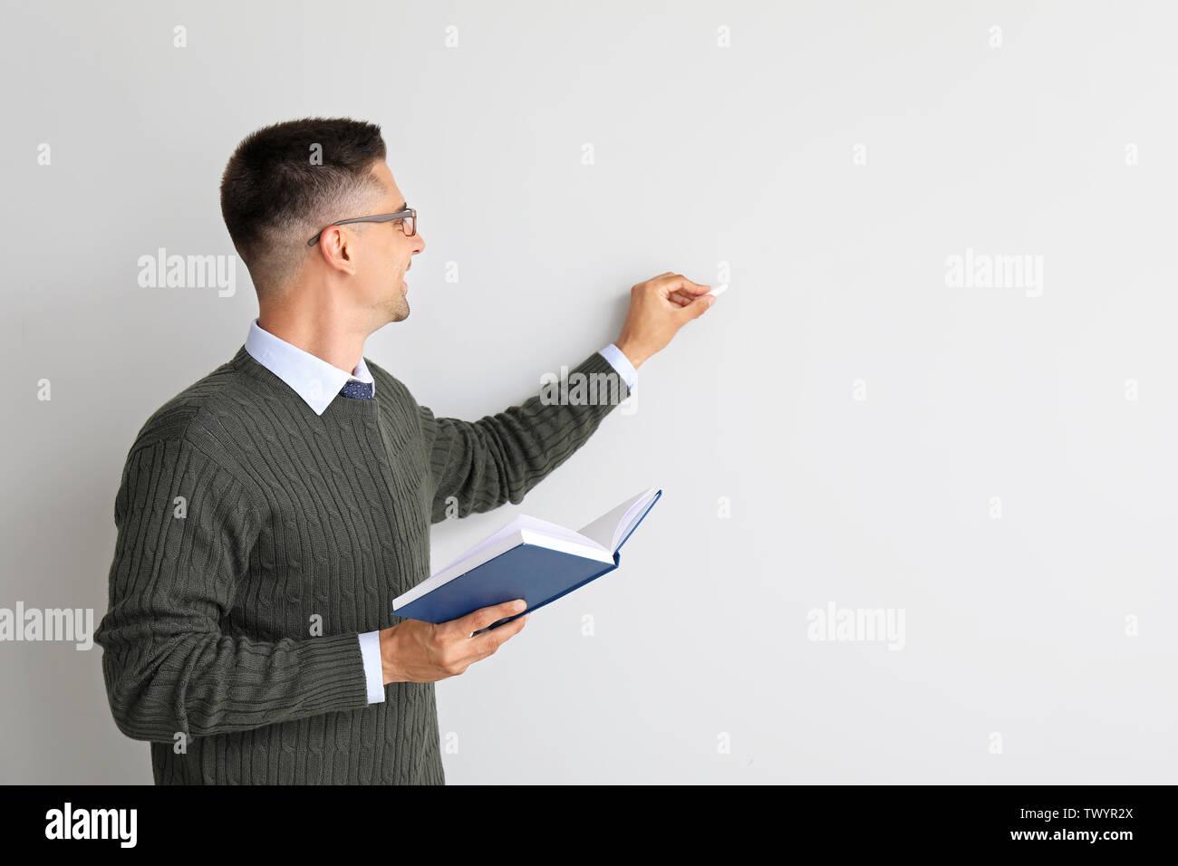 Beau mâle enseignant avec l'écriture de livre quelque chose contre fond blanc Photo Stock