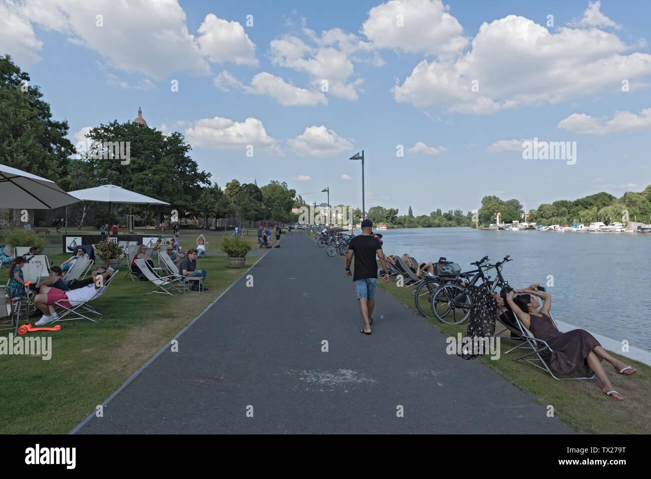 Les touristes dans des chaises longues au bord de l'eau sur la rivière principale de Francfort, Allemagne hoechst Photo Stock